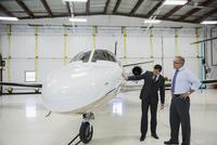 Pilot and manager examining corporate jet airplane hangar