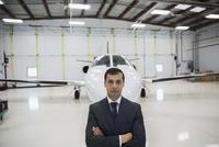Portrait serious pilot corporate jet airplane hangar