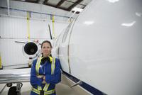 Portrait confident female mechanic leaning on corporate jet