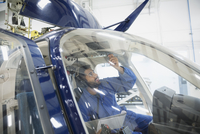 Mechanic checking instruments in helicopter cockpit
