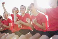 Girls soccer team cheering from bench.