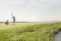 female golfers putting flagstick back in hole 11096020495| 写真素材・ストックフォト・画像・イラスト素材|アマナイメージズ