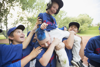 boys baseball team giving teammate a shoulder ride