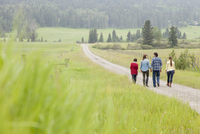 family of four walking along road on rural property