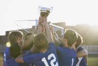Soccer team lifting trophy together.