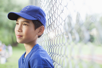 young male baseball player standing by fence
