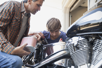 Father and son working on motorcycle
