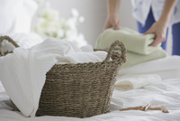 Woman folding clean laundry in bedroom.