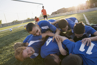 Soccer team piling up on each other after win.