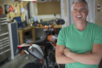 portrait of middle-aged man in garage with motorbike