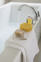 Close-up on white bath tub with bath products.