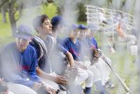 Boys baseball team talking while sitting on bench.