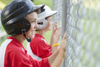 Two young male baseball players watching game from fence.