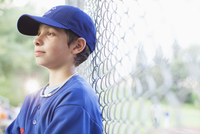 young male baseball player watching game from sidelines