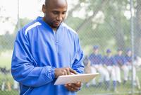 Baseball coach using pc tablet at ball game.
