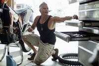 middle-aged man working on motorbike in garage