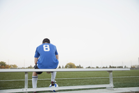 View from behind of one soccer player on bench.