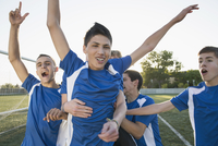 Soccer players cheering after win.