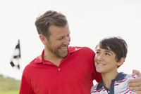 dad with arm around pre-teen son on golf course
