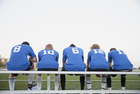 View from behind of soccer players on bench.