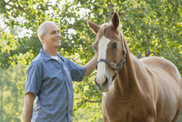 middle-aged man standing by horse on country property