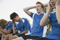 Teenage soccer players looking disappointed on bench.