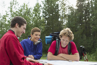 three hikers looking at trail map in the woods