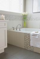 Details of modern tiled bathroom with calla lilies.