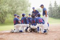 Coaches talking with boys baseball team