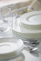 Stacked fine china dishes with silver edge on counter.