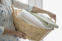 Mid-adult woman carrying wicker laundry basket.