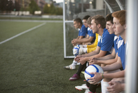 Profile of teenage soccer players on bench.