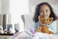 young girl in bed with teddy bear