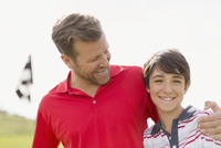 father with encouraging arm around son on golf course
