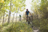 Two men riding on path in woods with mountain bikes.