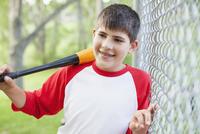 Young male baseball player with baseball bat.