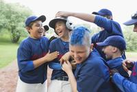 Boys baseball team celebrating after winning game.
