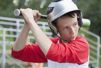 Twelve year old male baseball player ready to bat.