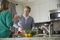 Woman with glass of wine while husband prepares salad
