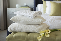 Pillow, blankets and lilies on footstool in bedroom