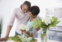 Man embracing woman as she arranges flowers in kitchen