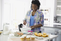 Woman mixing batter for cupcakes in kitchen