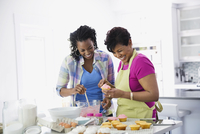 Mother and adult daughter baking cupcakes in kitchen 11096026693| 写真素材・ストックフォト・画像・イラスト素材|アマナイメージズ