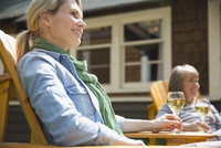 Smiling middle-aged woman drinking wine outdoors