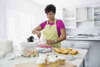 Woman mixing ingredients in bowl to decorate cupcakes 11096027125| 写真素材・ストックフォト・画像・イラスト素材|アマナイメージズ