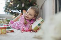 Girl opening Christmas gift at home 11096027617| 写真素材・ストックフォト・画像・イラスト素材|アマナイメージズ