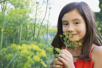 Girl holding fennel flower in garden