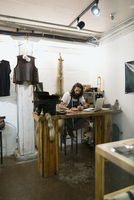 Leather shop owner entrepreneur working at laptop