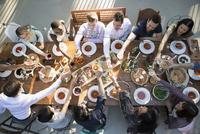 Friends toasting around long dining table at wedding reception 11096029607| 写真素材・ストックフォト・画像・イラスト素材|アマナイメージズ