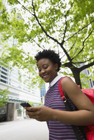 Smiling woman with backpack texting under city tree
